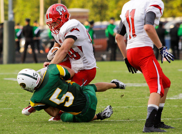 Floyd Central defensive back Evan Rue attempts to take down Madison wide receiver Trey Whalen during the first half of their game at Floyd Central on Friday. Staff photo by Christopher Fryer