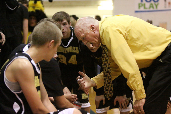 Henryville first year coach Dan Carmony talks things over with his team during a timeout Tuesday night at Silver Creek. Staff photo by C.E. Branham