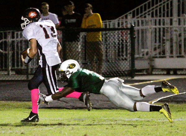 Floyd Central senior Gabriel Kennedy dives to tackle Bedford North Lawrence junior Andrew Carrico during their game at Floyd Central on Friday. Staff photo by Christopher Fryer