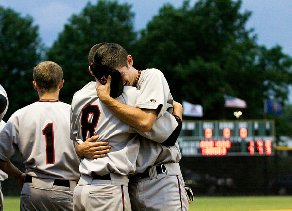 New Albany junior Dale Brummett, right, and senior Tucker Marcum comfort each other after the Bulldogs' 7-1 loss to Jeffersonville in the championship game of the New Albany Sectional on Monday. Staff photo by Christopher Fryer
