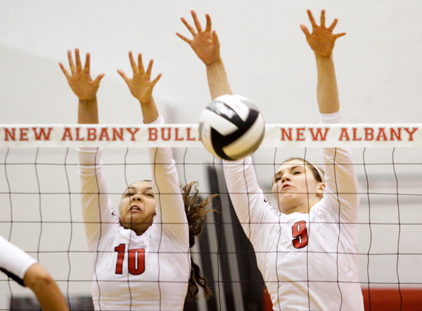 New Albany sophomores Audrey Donastorg, left, and Alexis Lete block a shot during their home match against Brownstown Central on Thursday. Staff photo by Christopher Fryer