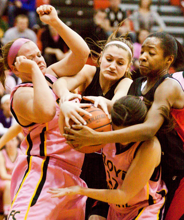 Floyd Central guards Brooke Hinton, left, and Shelby Rost fight for possession of a loose ball with New Albany guard Lauren Camm and forward Brianne Nixon, right, during their game at New Albany on Saturday. New Albany won the game in double overtime, 69-64. Staff photo by Christopher Fryer