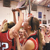 The Borden Lady Braves let out a cheer as senior Erin Mikel hoists the 1A sectional championship trophy Saturday night at Borden.  The Lady Braves defeated county rival New Washington 45-34.  Staff photo by C.E. Branham