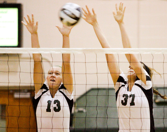 Floyd Central's Remi Bowman, left, and Gwyn Jones attempt to block a shot during the second game of their home match against New Albany on Thursday. Staff photo by Christopher Fryer