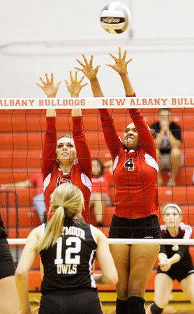 New Albany seniors Olivia Balmer, left, and Kelsey Guess attempt to block a Seymour shot during their home match on Thursday. Seymour took the match in three sets, 25-23, 25-23, 25-14. Staff photo by Christopher Fryer