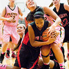 New Albany forward Brianne Nixon and Floyd Central center Niki Bruno struggle for possession of a loose ball during their game at New Albany on Saturday. New Albany won the game in double overtime, 69-64. Staff photo by Christopher Fryer