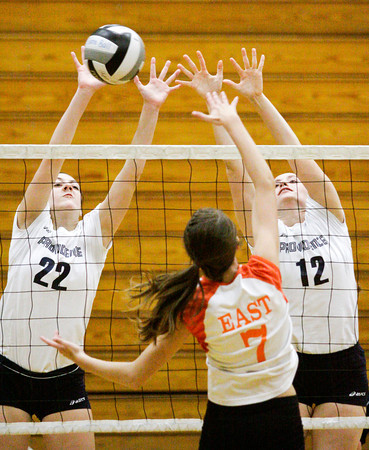 Providence senior Maile Daniel, left, and sophomore Jacquie Hornung attempt to block a shot during their match against Columbus East at the annual Providence Early Bird Invitational on Saturday. Columbus East won the match in three sets. Staff photo by Christopher Fryer