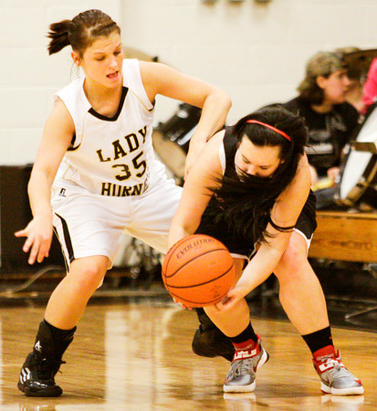 Henryville (35) and Rock Creek (24) struggle for a loose ball during the second half of their game at Henryville on Thursday. Henryville won the game, 62-25. Staff photo by Christopher Fryer
