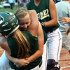 Floyd Central senior Samantha Feather hugs teammate Briana Mayfield after Mayfield drove in the winning run over Bedford North Lawrence in the 4A Sectional championship. Staff photo by C.E. Branham