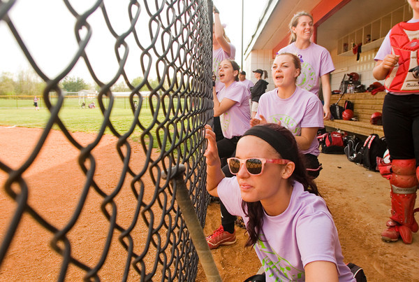 New Albany players cheer on their teammates from their dugout during their home game against Providence on Tuesday. Players and fans wore purple and lime green to the game to support New Albany's Sydney Michell, who is currently battling hodgkins lymphoma. Staff photo by Christopher Fryer