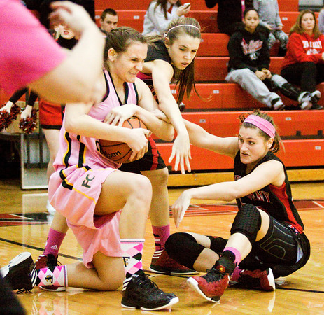 Floyd Central center Tori Kingsley struggles with New Albany guards Jenna Shine, center, and Lauren Camm for possession of a loose ball during their game at New Albany on Saturday. New Albany won the game in double overtime, 69-64. Staff photo by Christopher Fryer