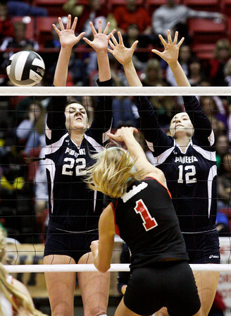 Providence junior Maile Daniel, left, and freshman Jacquie Hornung attempt to block a shot by Wapahani senior Aubreigh Applegate during their Class 2A state championship match at Worthen Arena in Muncie on Saturday. Wapahani won the match in 4 sets. Staff photo by Christopher Fryer