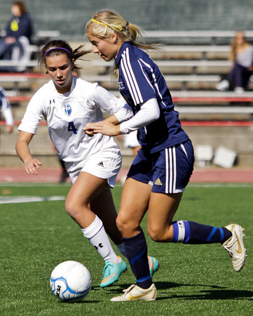 Providence defender Maryashly Betz drives the ball past by Mishawaka Marian forward D.J. Veldman during the first half of their Class A state championship game in Indianapolis on Saturday. Mishawaka Marian won the game, 2-0. Staff photo by Christopher Fryer