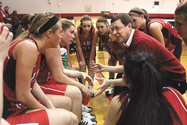 Borden coach Terry Rademacher talks with his team during a timeout in the 1A sectional final against New Washington Saturday night.  The Lady Braves won 45-34.  Staff photo by C.E. Branham