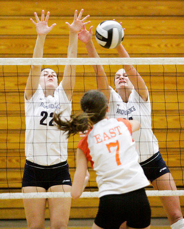 Providence senior Maile Daniel, left, and junior Haley Libs attempt to block a shot during their match against Columbus East at the annual Providence Early Bird Invitational on Saturday. Columbus East won the match in three sets. Staff photo by Christopher Fryer