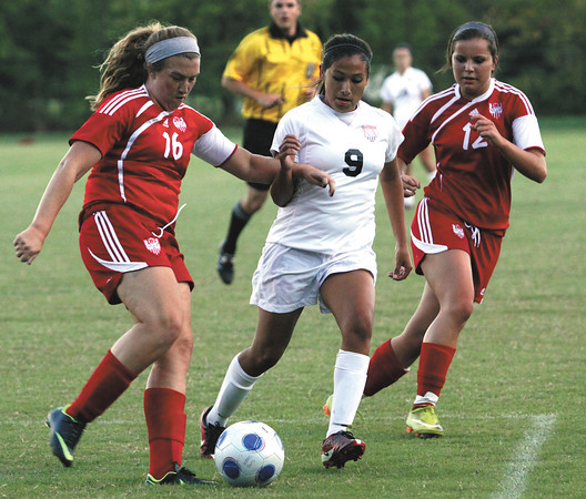 New Albany junior Stephanie Iglesias, center, and Jeffersonville defender Kealey Vance battle for the ball in a match Wednesday night at New Albany. Staff photo by C.E. Branham
