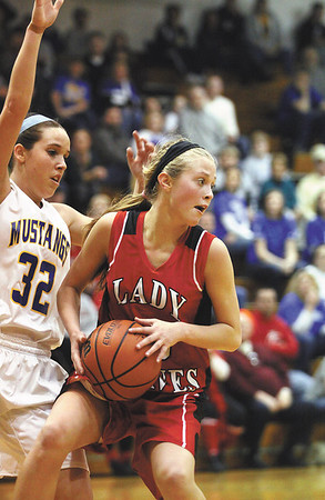 Borden guard Shelby Kirchgessner looks to pass after being stopped by New Washington guard Ashley Johnson.  Staff photo by C.E. Branham