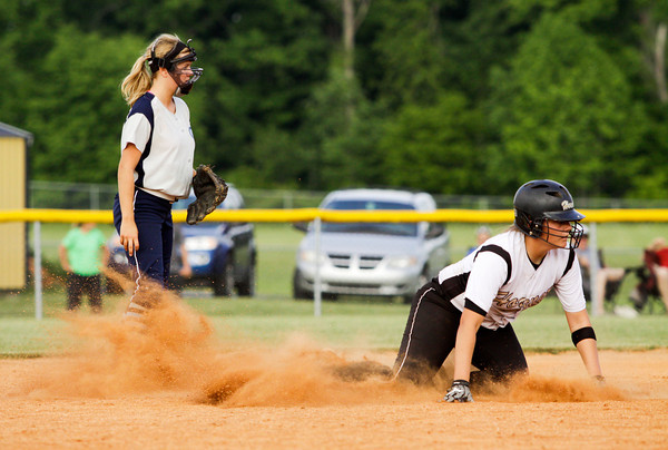 Providence senior Morgan Boone, left, and Henryville freshman Emma Hendricks watch a play at first base after Hendricks slid safely into second base during their game at the Eastern High School sectional tournament on Monday. Providence won the game, 10-9. Staff photo by Christopher Fryer