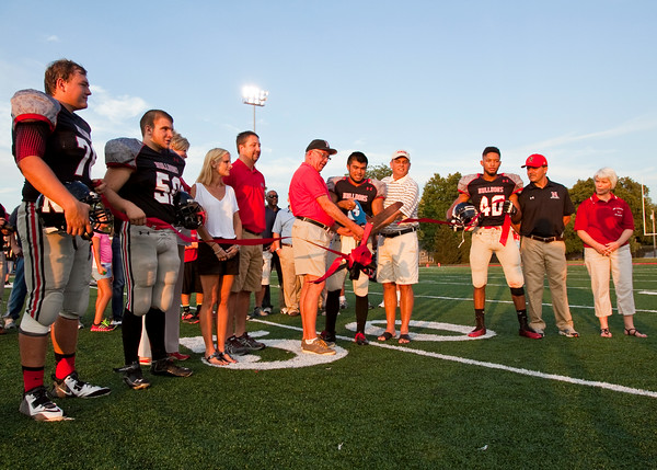 Administrators, coaches and players participate in a ribbon cutting ceremony to mark the first game on the new artificial turf at New Albany's Buerk Field before the start of the Bulldogs' game against Castle on Friday. Staff photo by Christopher Fryer