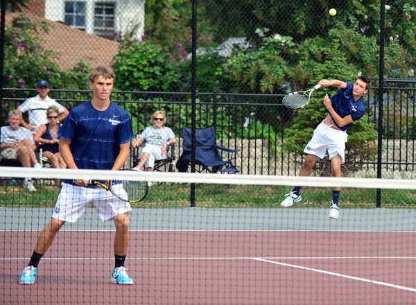 Pioneer seniors Ryan Day serves the ball as teammate Jacob Quinkert awaits the Bulldog return during the No. 1 doubles finals in the New Albany Invitational Saturday morning. Providence earned the bested New Albany 6-3, 6-4, 6-4. As a team the Pioneers earned the Invitational victory with 52 points. <br /> Staff photo by Tyler Stewart