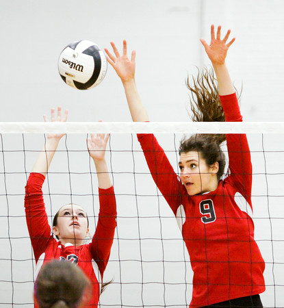 New Albany sophomore Sadie Meyer, left, and senior Alexis Lete attempt to block a shot during the Bulldogs' game at Providence on Tuesday. Providence took the match in three sets. Staff photo by Christopher Fryer
