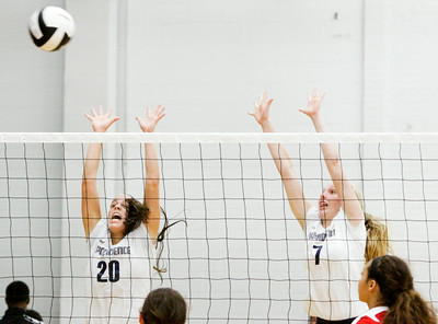 Providence senior Patricia Mattingly, left, and junior Mandy Barney attempt to block a shot during the Pioneers' home game against New Albany on Tuesday. Providence took the match in three sets. Staff photo by Christopher Fryer