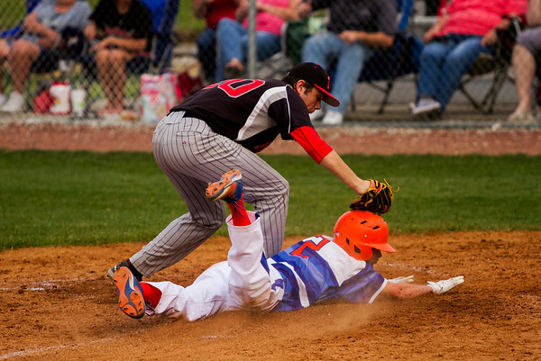 Silver Creek's Elijah Bays slides safely into home past Borden's Caleb Hart during the Dragons' home game against the Braves in Sellersburg on Tuesday. Staff photo by Christopher Fryer