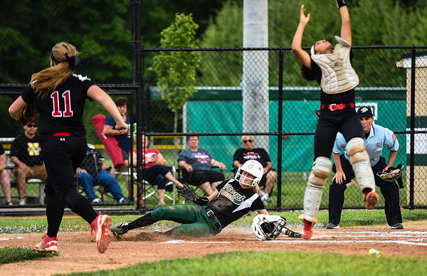 Floyd Central centerfielder Jensen Striegel slides past New Albany catcher Terah Crosier to score off an RBI-double by Gabbi Jenkins during the Highlanders' 5-0 win over the Bulldogs in the semifinal of the Hoosier Hills Conference tournament Wednesday night. Staff photo by Tyler Stewart