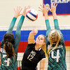 Don Knight | The Herald Bulletin<br /> Madison-Grant's Maddie Barnhart attacks the ball getting it past the block of Brinkley Gary and Bronwyn Boots during the county volleyball tournament at Elwood on Saturday.