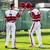 Jeffersonville's Bailey Falkenstein, left, bumps helmets with Michael Minton after he scored a run during the Red Devils' game against Seymour on Thursday. Staff Photo By Josh Hicks