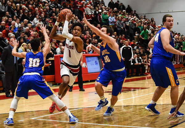 New Albany forward Romeo Langford splits the Carmel defenders as he heads toward the basket during the Bulldogs' 55-52 win over the Greyhounds on Tuesday. Staff photo by Tyler Stewart
