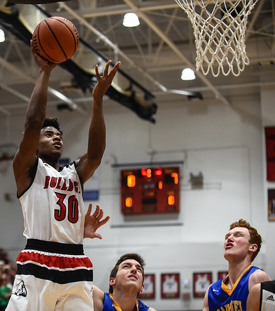 New Albany forward Julien Hunter puts up a shot after an offensive rebound over the Carmel defense during the Bulldogs' 55-52 win over the Greyhounds on Tuesday. Staff photo by Tyler Stewart