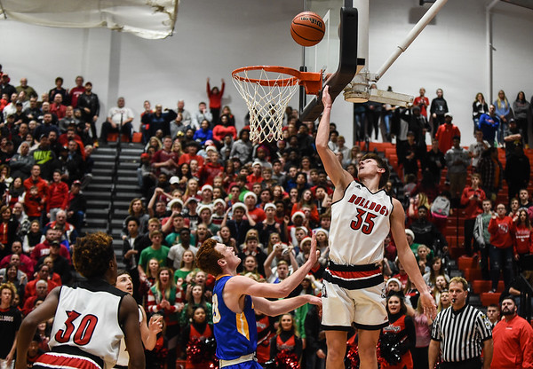 New Albany forward Blake Murphy puts a reverse layup past the Carmel defender during the Bulldogs' 55-52 win over the Greyhounds on Tuesday. Staff photo by Tyler Stewart