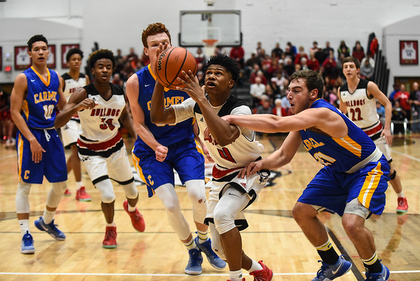 New Albany guard Kobe Stanton breaks through the Carmel defense during the Bulldogs' 55-52 win over the Greyhounds on Tuesday. Staff photo by Tyler Stewart