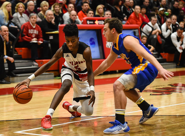 New Albany Sean East cuts back on Carmel defender Alex Falender during the Bulldogs' 55-52 win over the Greyhounds on Tuesday. Staff photo by Tyler Stewart