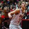 New Albany guard Derrick Stevenson is blocked out by Jeffersonville forward Gerrin Moore during the Bulldogs' 67-56 win over the Red Devils on Friday. Staff photo by Tyler Stewart