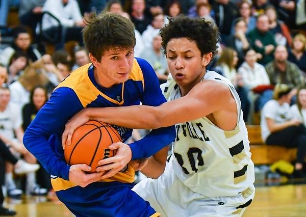 Henryville guard Nick Walker attempts to strip the ball from New Washington guard Brandon Horton during the Hornets' 57-33 win over the Mustangs on Friday. Staff photo by Tyler Stewart