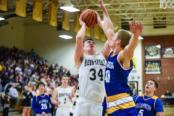 Henryville forward Thomas Green takes the ball up against New Washington forward Zach Moore during the Hornets' 57-33 win over the Mustangs on Friday. Staff photo by Tyler Stewart
