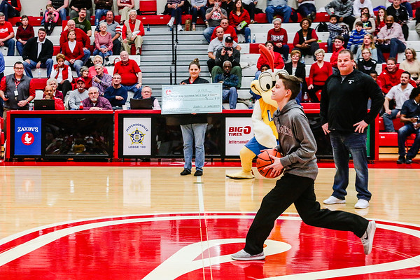 Jared Fleton steps up to the half court line to take a shot to win $5,000 sponsored by Zaxby's during halftime of Jeffersonville's game against Ballard at Johnson Arena on Friday. Staff Photo By Josh Hicks