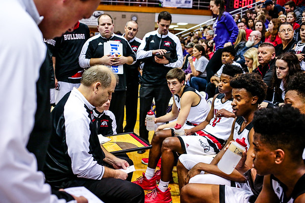 New Albany's Coach Jim Shannon leads the Bulldogs into the second quarter of the team's 89-52 Class 4A Sectional Semifinal win over Bedford at Lloyd E. Scott Gymnasium in Seymour on Friday. Staff Photo By Josh Hicks