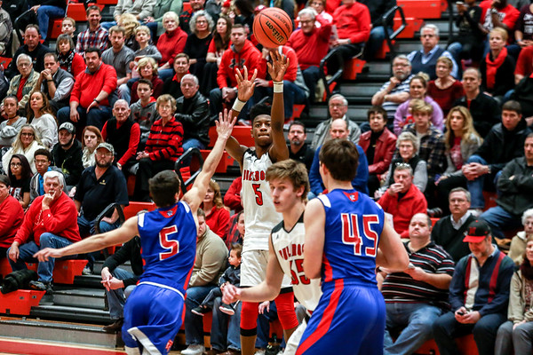 New Albany's Sean East makes a long distance shot over Jennings County's Chase Ketcham while Bulldog Blake Murphy picks off Panther defender Bret Sawyer during the Bulldogs' game against Jennings County at the Doghouse on Thursday. Saff Photo By Josh Hicks