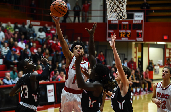 Jeffersonville guard Jacob Jones gets the layup over the Southport defense during the Red Devils' 65-52 win over the Cardinals on Wednesday. Staff photo by Tyler Stewart