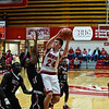 Jeffersonville forward Bailey Falkenstein takes the short-range jumpshot over the Southport defenders during the Red Devils' 65-52 win over the Cardinals on Wednesday. Staff photo by Tyler Stewart