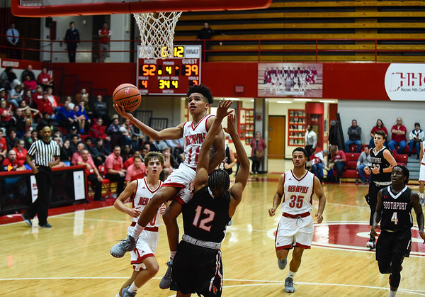 Jeffersonville guard Jacob Jones draws a foul on Southport defender Brevin Jefferson during the Red Devils' 65-52 win over the Cardinals on Wednesday. Staff photo by Tyler Stewart
