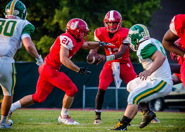 Jeffersonville's Shaun Wimberly Jr. hands the ball off to Kameron Fuller during the Red Devils' game against Floyd Central on Friday.