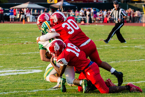 Jeffersonville's Jaylen Bells, left, and Dylan Jolley-Little tackle Floyd Central's Zach Rodgers during the Red Devils' game against the Highlanders on Friday.