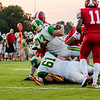 Floyd Central's Jason Cundiff rolls over Clay Miller, landing inches away from the endzone during the Highlanders' game against Jeffersonvill on Friday.