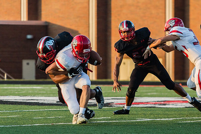 New Albany's Kaleb Scalf makes a tackle during the Bulldogs' game against Madison on Friday.