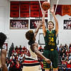 Floyd Central center Trevor Apple pulls up for a short-range shot over New Albany defender Julien Hunter during the Bulldogs' 65-42 win over the Highlanders on Friday. Staff photo by Tyler Stewart