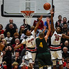 New Albany forward Julien Hunter stops the shot by Floyd Central guard Matt Weimer during the Bulldogs' 65-42 win over the Highlanders on Friday. Staff photo by Tyler Stewart